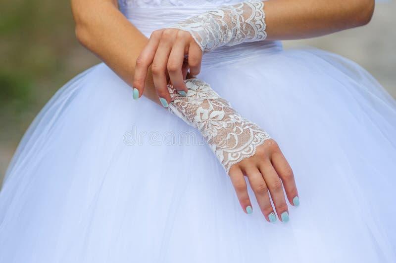 有美好的修指甲的年轻新娘手穿戴手套 免版税库存图片