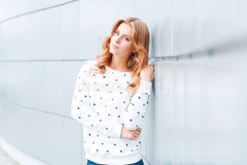 有美好的微笑的俏丽的典雅的正面年轻白肤金发的妇女在户内白色现代墙壁附近的一件时兴的套头衫 库存照片