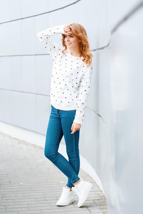 有美好的微笑的俏丽的正面年轻女人在时兴的蓝色牛仔裤和时髦白色运动鞋的一件时髦的毛线衣 库存照片