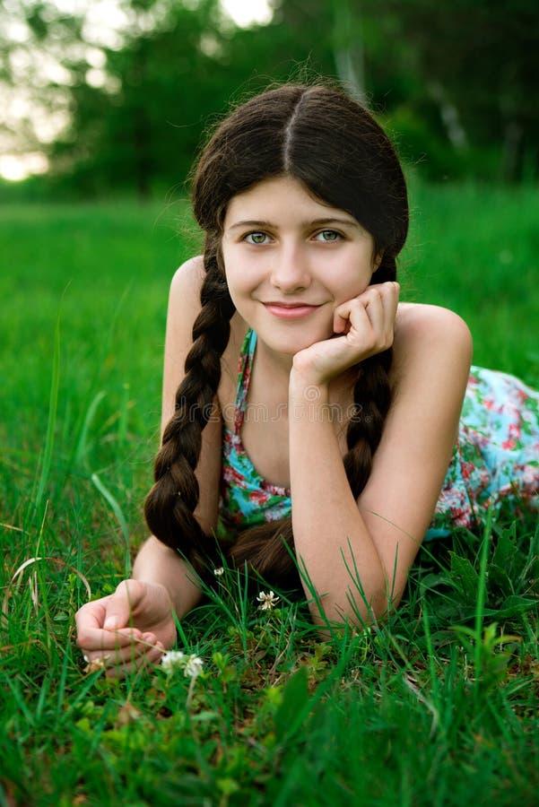 有美好的微笑的好女孩在gr摆在 免版税图库摄影