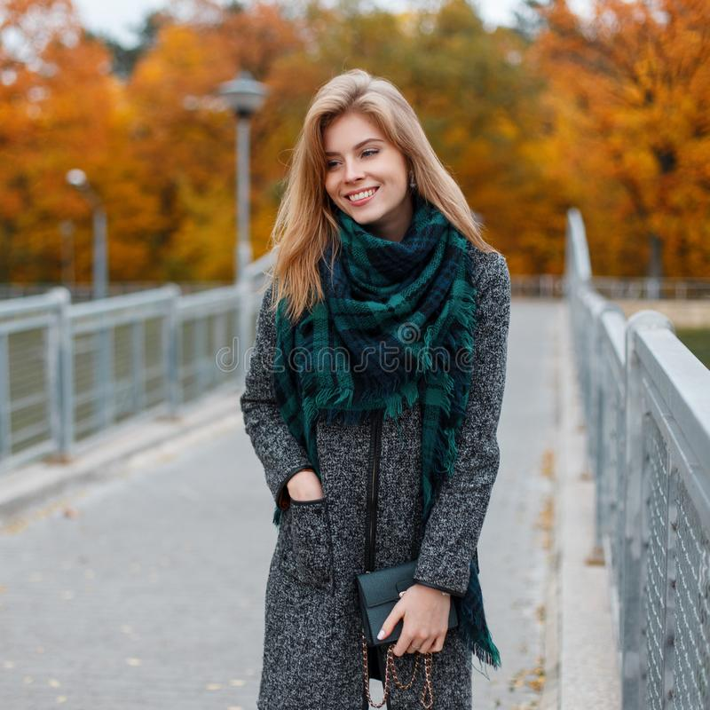 有美好的微笑的年轻愉快的妇女与在时髦典雅的衣裳的金发有提包的站立 图库摄影