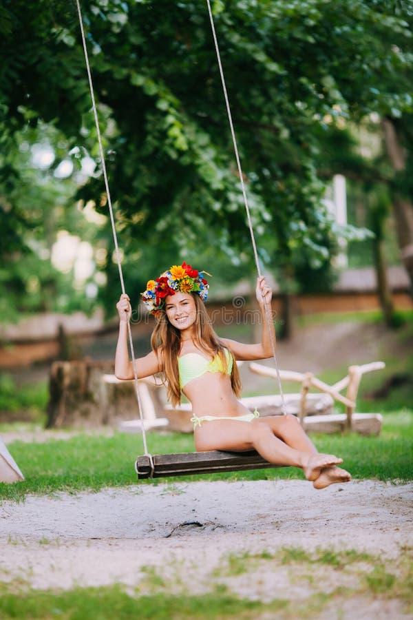 有美好的微笑的美丽的女孩在摇摆在户外夏日 库存图片