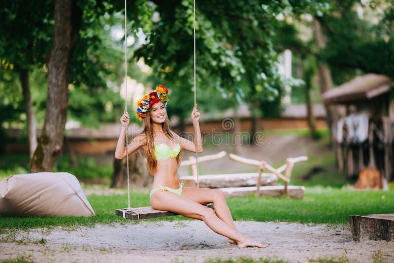 有美好的微笑的美丽的女孩在摇摆在户外夏日 图库摄影