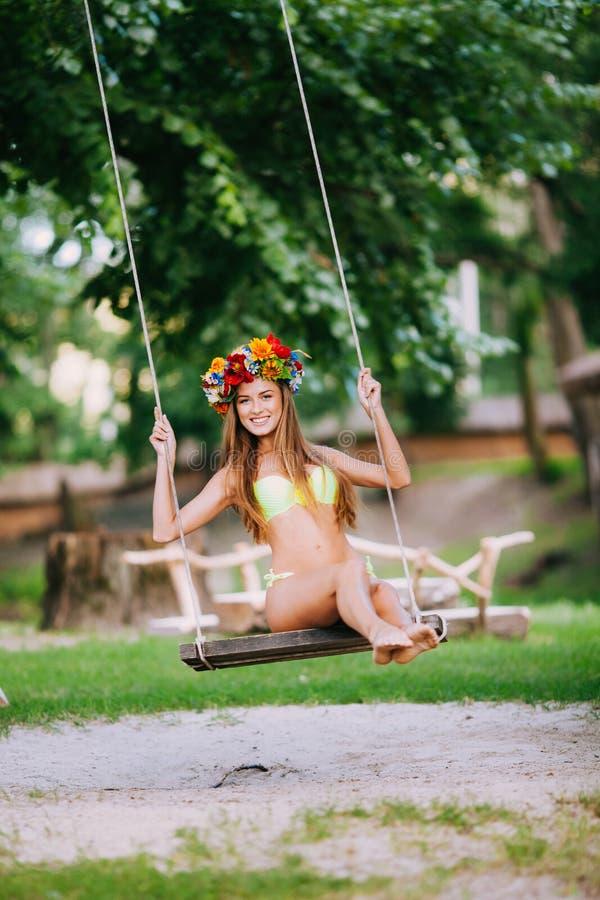 有美好的微笑的美丽的女孩在摇摆在户外夏日 免版税库存图片