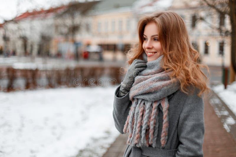 有美好的微笑的走动时兴的俏丽的年轻女人在一条时髦的灰色围巾的一件灰色典雅的外套在手套 库存照片
