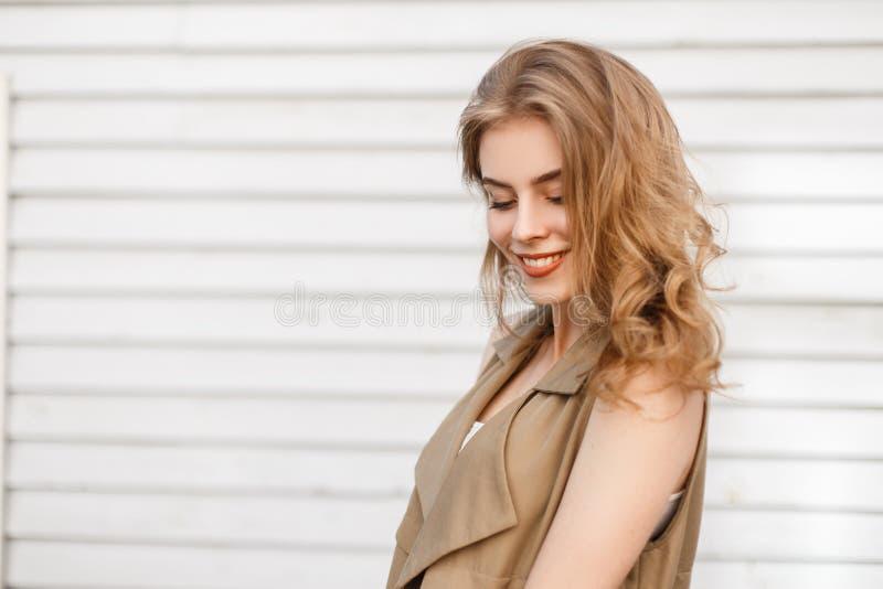 有美好的微笑的迷人的可爱的年轻女人在时髦的夏天衣裳在白色木葡萄酒墙壁附近站立户外 免版税库存图片