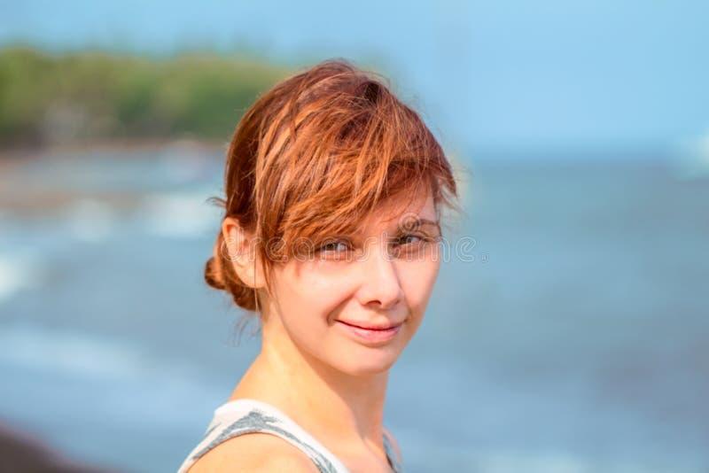 有美好的微笑的轻松的妇女由海 海滩女孩头发红色 免版税库存照片