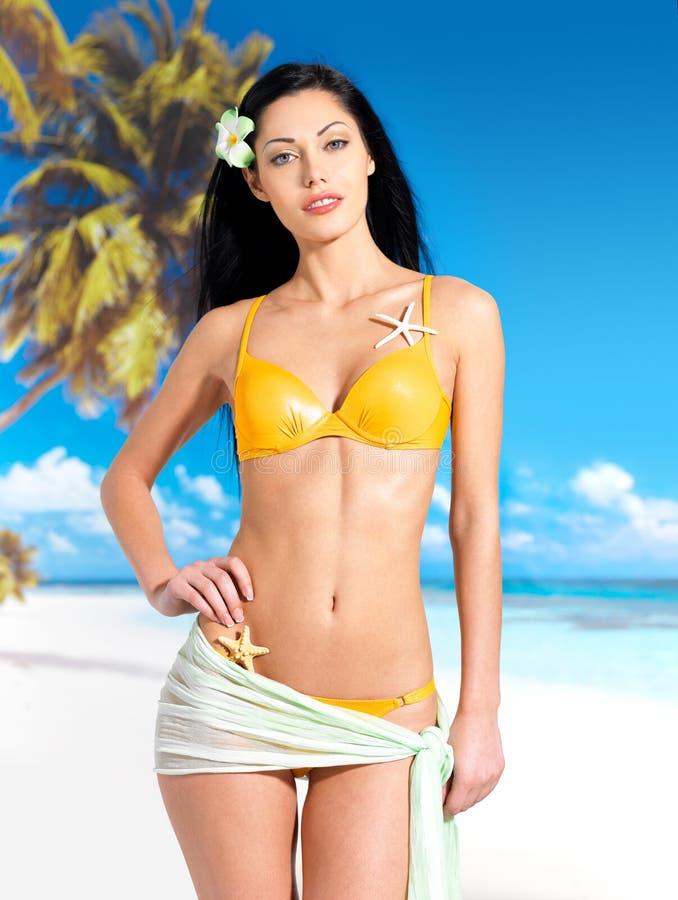 有美好的机体的妇女在海滩的比基尼泳装 免版税库存照片