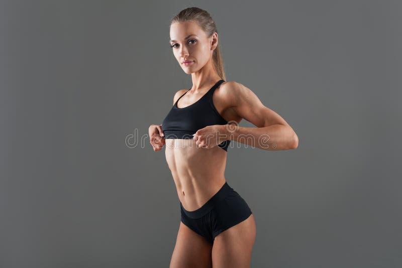 有美好的精瘦,强健的身体的一个美丽的女孩培养背心炫耀美丽的腹肌