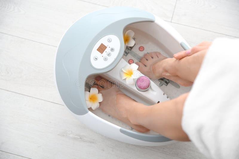 有美好的腿的妇女使用在家脚浴,特写镜头 库存图片