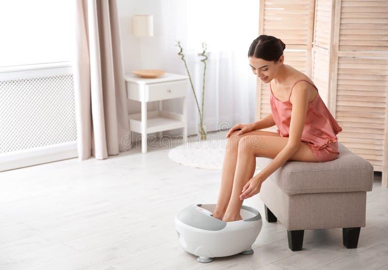 有美好的腿的妇女使用脚浴在家 免版税库存照片