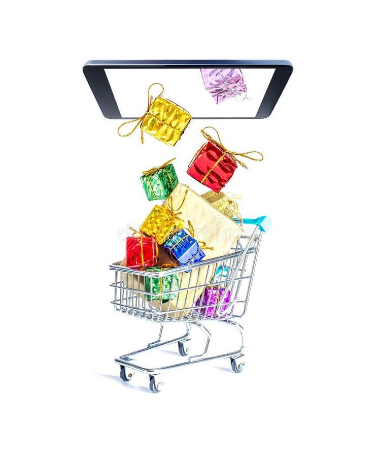 有美好的金黄弓的多彩多姿的礼物盒飞行在智能手机屏幕外面并且落入礼物充满的购物车 免版税库存图片