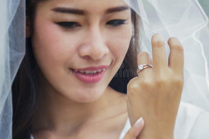 有美好的钻戒的美好的新娘手在白色礼服 库存照片