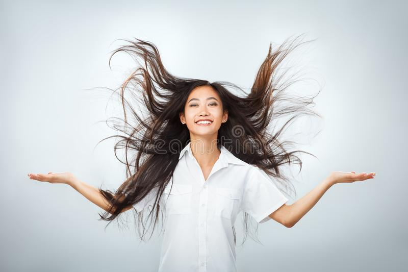 有美好的飞行长的头发的愉快的年轻亚裔妇女 库存图片