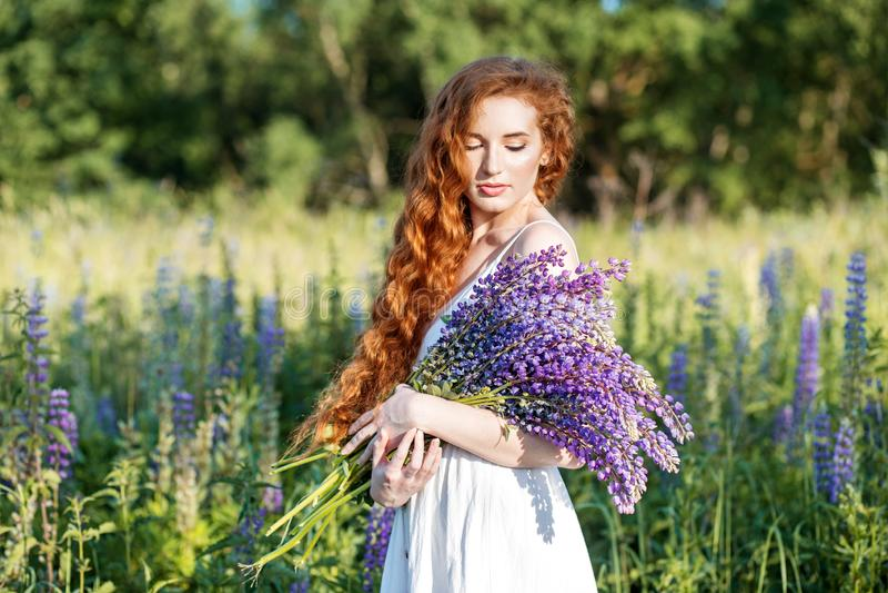 有羽扇豆花花束的美女  概念夏天、生活方式、旅行和秀丽 库存图片