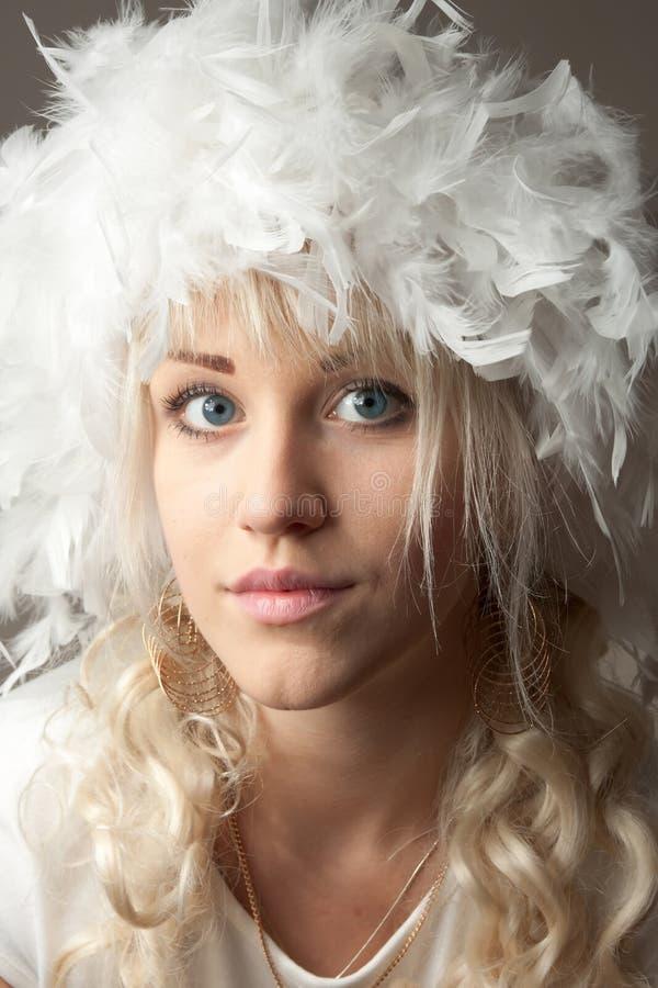 有羽毛帽子的可爱的少妇 免版税库存照片