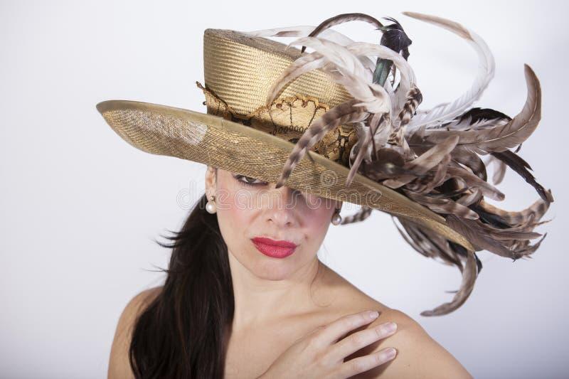 有羽毛帽子的美女和红色嘴唇 减速火箭的方式 免版税库存照片