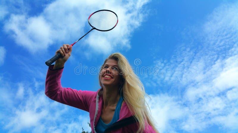 有羽毛球拍的白肤金发的女孩在手上 免版税图库摄影