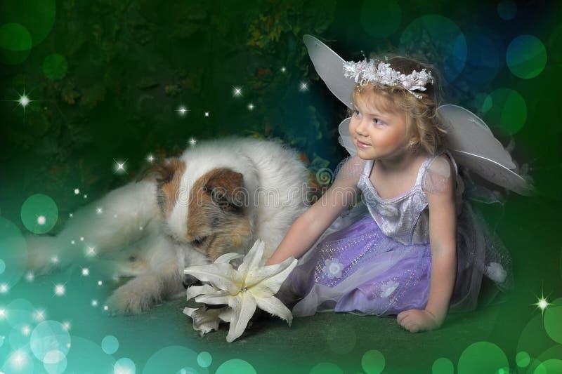 有翼和狗的小女孩 库存照片