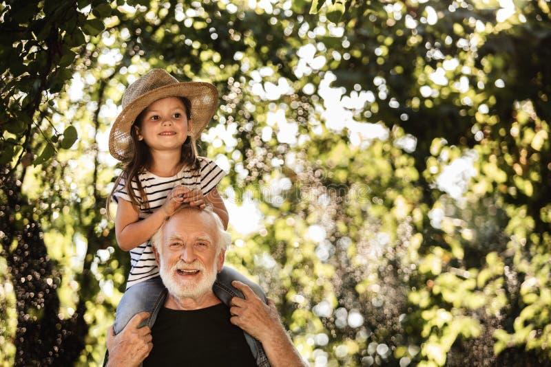 有老人的女孩获得乐趣在庭院 图库摄影