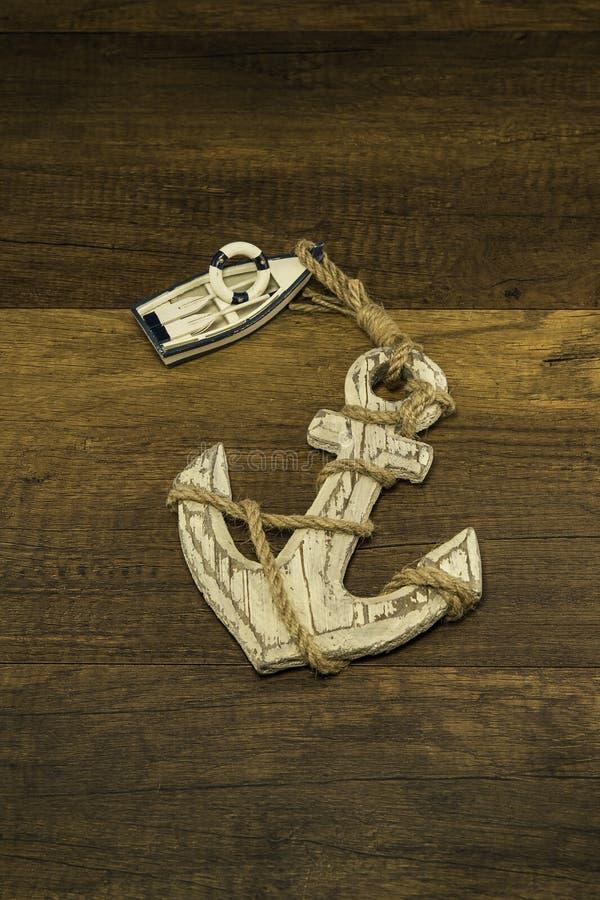 有老大船锚的小白色船在木背景 库存图片