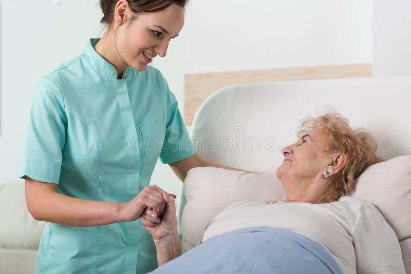 有老妇人的支援护士 免版税图库摄影
