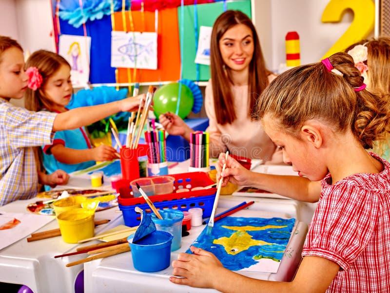 有老师妇女绘画的孩子在纸在幼儿园 免版税库存图片