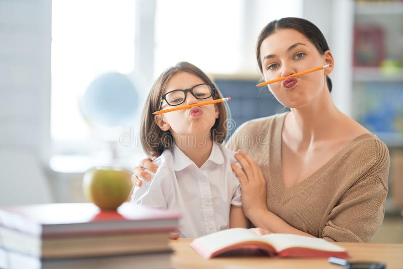 有老师的女孩在教室 免版税库存照片