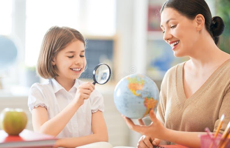 有老师的女孩在教室 免版税库存图片