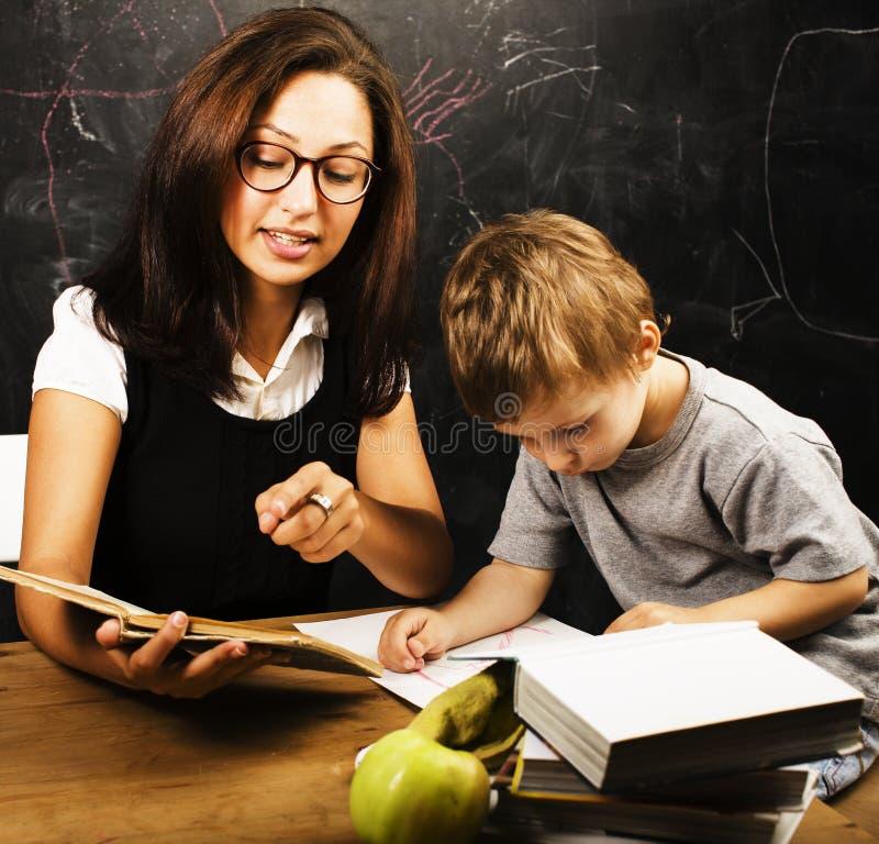 有老师的小逗人喜爱的男孩在教室 免版税库存照片