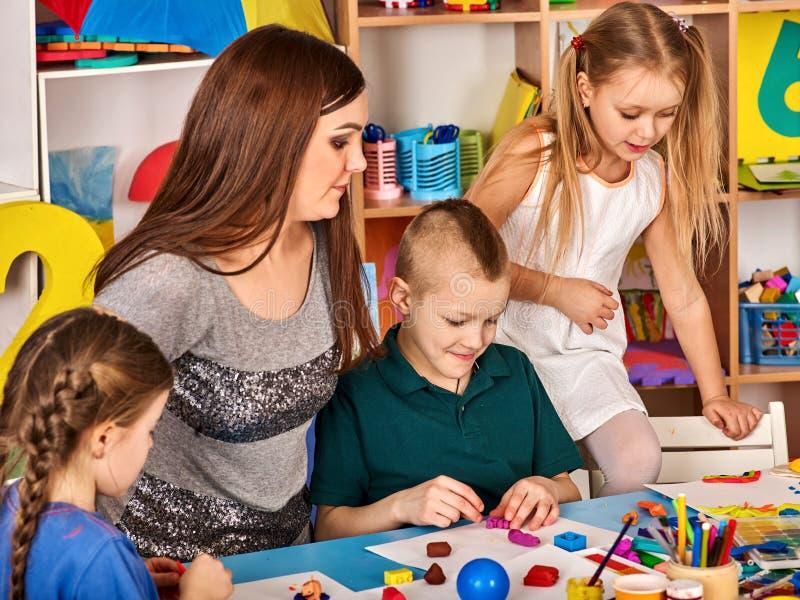 有老师绘画的小学生在艺术学校分类 免版税图库摄影