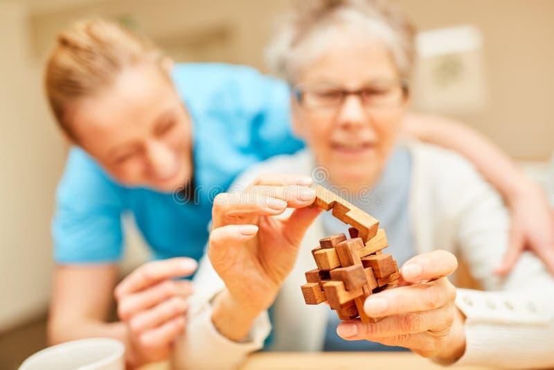 有老年痴呆戏剧的资深妇女与木难题 免版税库存照片