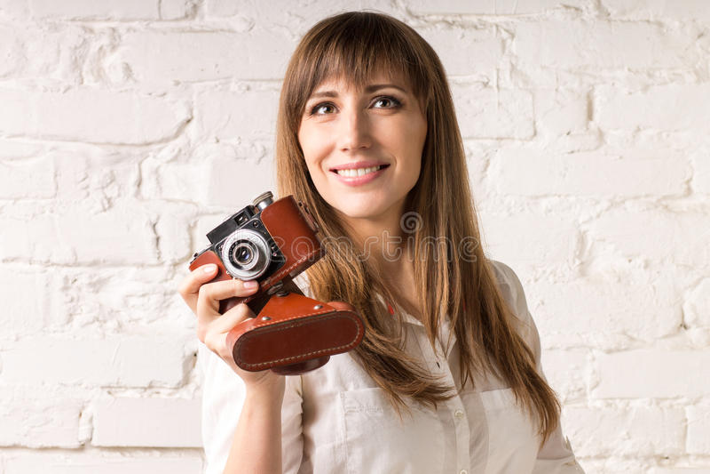 有老影片照相机的俏丽的微笑的妇女在白色砖墙上 图库摄影