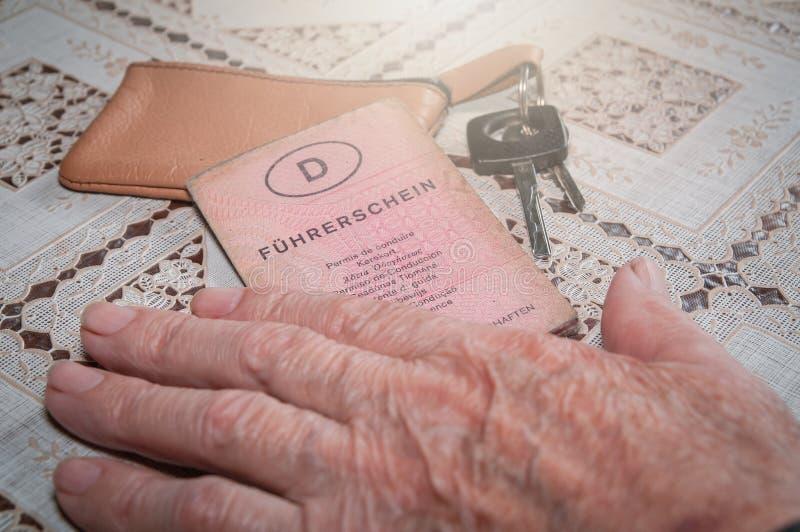 有老德国驾照'Führerschein'和汽车钥匙的资深手 免版税库存照片