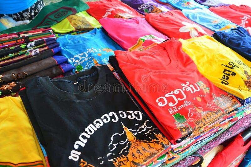 有老挝人旅游胜地的五颜六色的T恤杉在万象,老挝人筛选打印被卖在纪念品店PDR首都 免版税库存图片