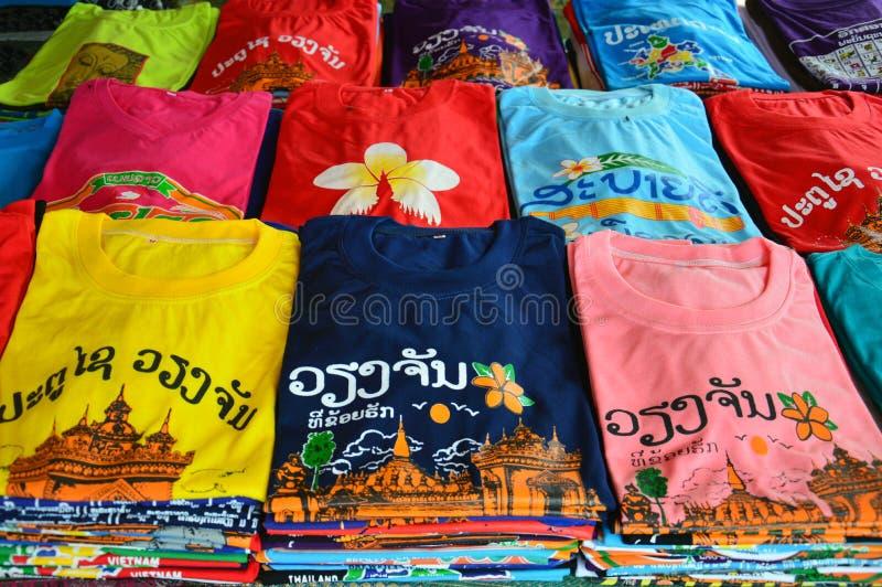 有老挝人旅游胜地的五颜六色的T恤杉在万象,老挝人筛选打印被卖在纪念品店PDR首都 免版税图库摄影