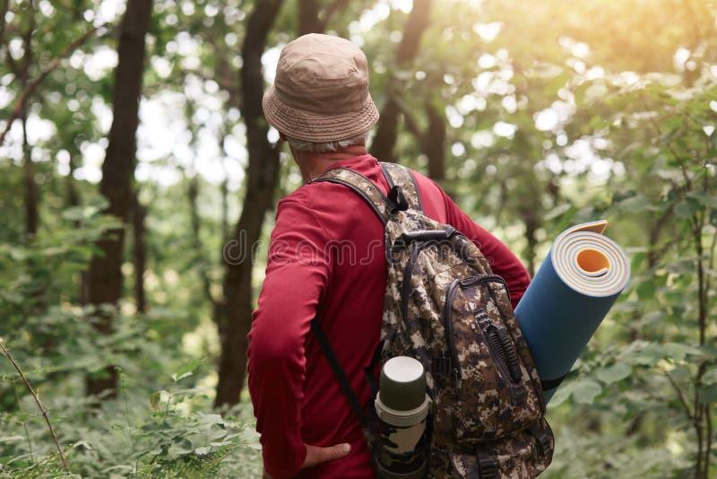 有老的人室外射击与热水瓶的袋子和睡觉垫、佩带的米黄帽子和红色运动衫,寻找冒险  库存图片