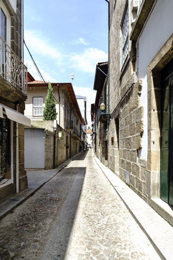 有老花岗岩石头房子门面的狭窄的鹅卵石胡同在老镇叫吉马朗伊什 免版税库存图片