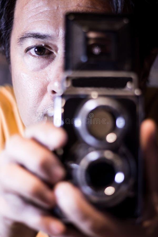 有老葡萄酒照相机的人在手上 供以人员眼睛的焦点 葡萄酒传统化了人摄影师照片有老TLR孪生透镜反射的 免版税库存照片