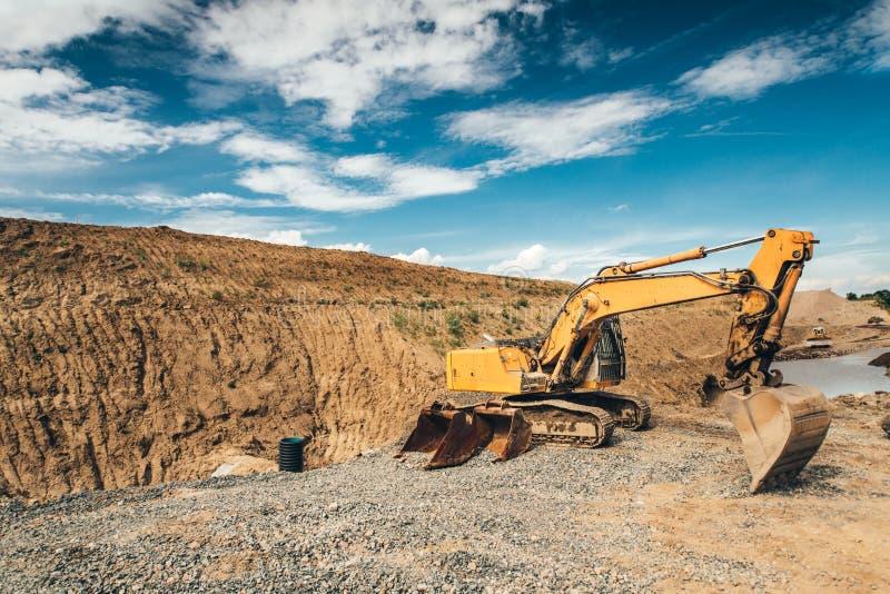 有耐用瓢移动的地球和装货倾销者卡车的挖掘机在高速公路建筑的长跑训练期间 库存照片