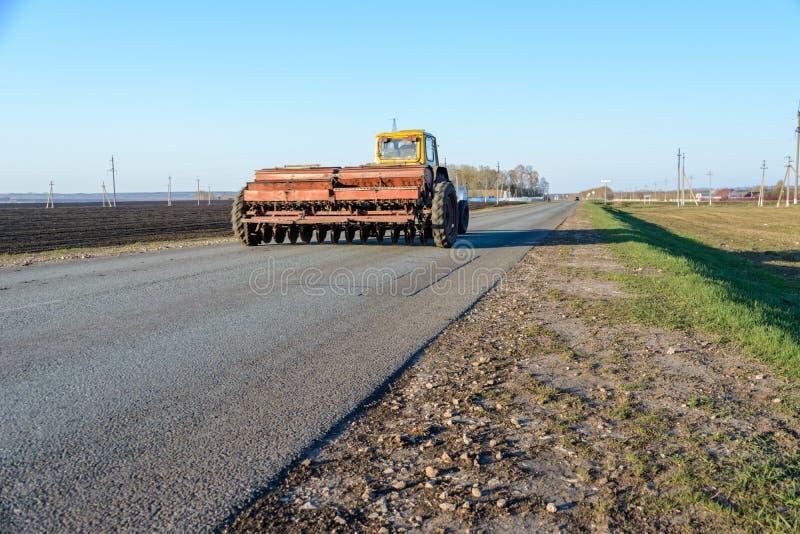 有耕地机回归的一台拖拉机与沿一条农村路的一次播种的竞选 拖拉机完全地阻拦了路 免版税图库摄影