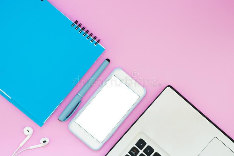 有耳机、笔记本和笔记薄的智能手机在桃红色背景 顶视图 工作空间舱内甲板位置布局 库存图片