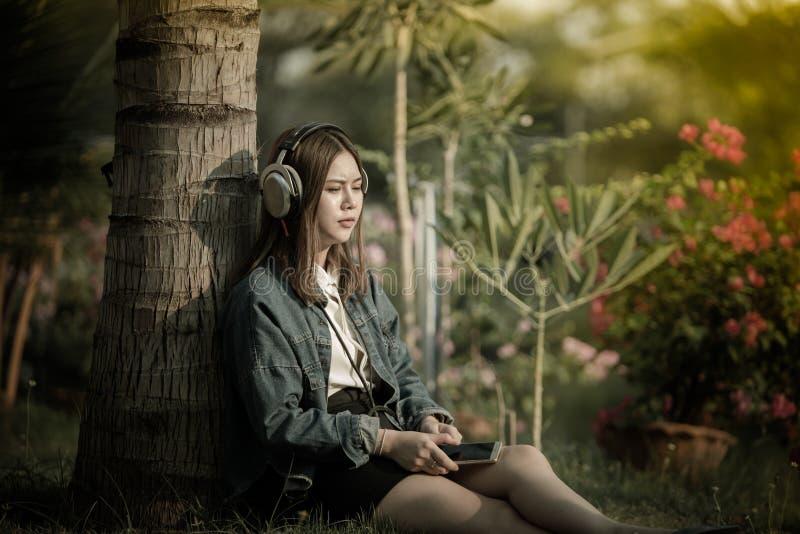 有耳机伤心的妇女和哭泣她使用智能手机听哀伤的音乐 免版税图库摄影