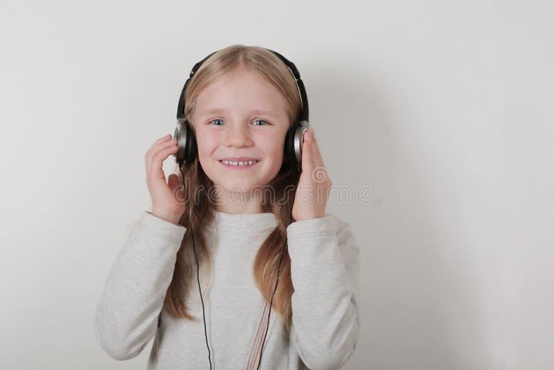 有耳机听的音乐和唱歌的白肤金发的女孩 做摇滚n卷标志的逗人喜爱的小女孩 库存图片