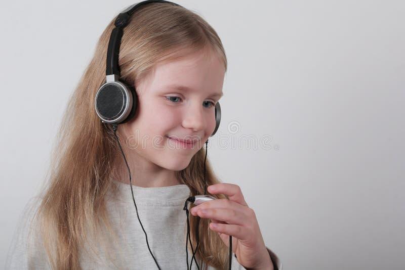 有耳机听的音乐和唱歌的白肤金发的女孩 做摇滚n卷标志的逗人喜爱的小女孩 库存照片