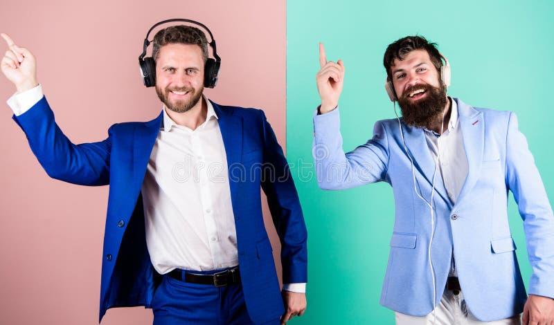 有耳机听的音乐的商人 同事听到音乐 音乐放松 正式人有胡子的面孔 免版税图库摄影