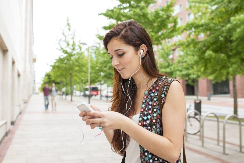 有耳机听的音乐的微笑的妇女,在街道 免版税图库摄影