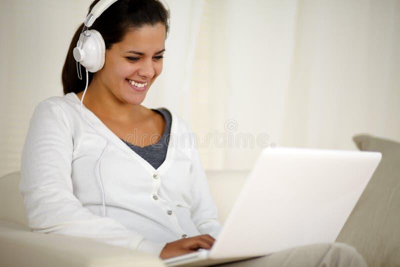 有耳机听的音乐的微笑的少妇 免版税库存照片