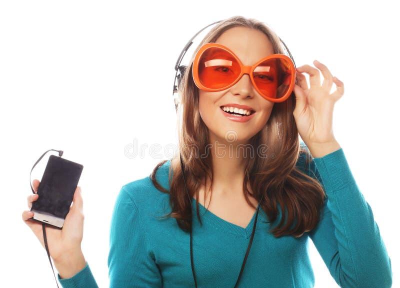有耳机听的音乐的年轻愉快的妇女 库存图片