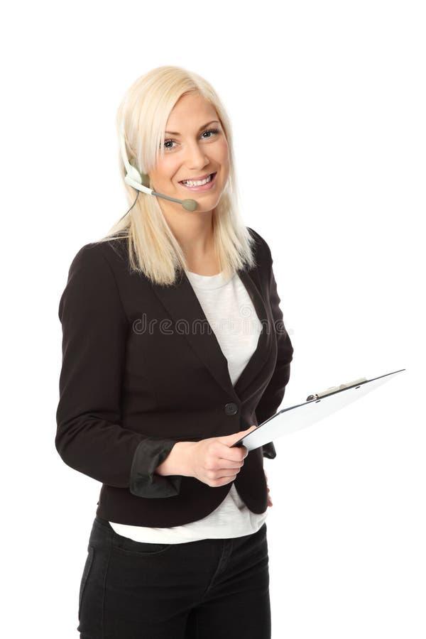有耳机和剪贴板的可爱的女商人 库存照片